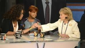 Oprah Winfrey, left, grasps hands with Barbara Walters,