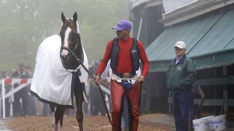 Exercise rider Willie Delgado, center, leads Kentucky Derby