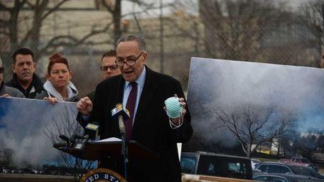 Sen.Charles Schumer speaks holding an air filtration mask