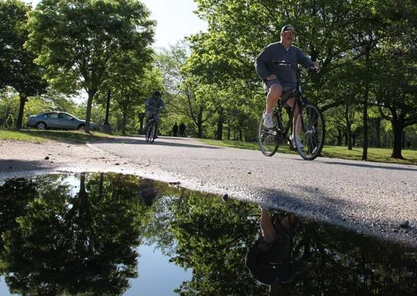 Bicyclists are reflected in a puddle after heavy