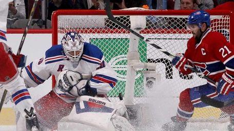 Goaltender Henrik Lundqvist of the Rangers dives for