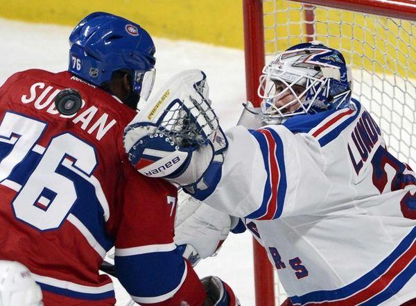 Rangers goalie Henrik Lundqvist, right, reaches for a