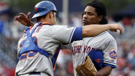 Mets catcher Anthony Recker, left, greets relief pitcher