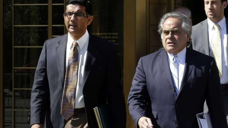 Conservative scholar and filmmaker Dinesh D'Souza, left, accompanied