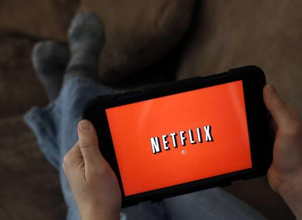 A person displays Netflix on a tablet in