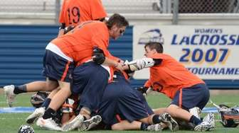 Mahasset players congratulate their goalie John Young on