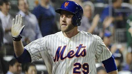 Mets' Eric Campbell is congratulated at the dugout
