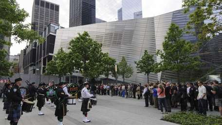 A pipe and drums band plays as members