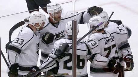 The Los Angeles Kings gather around center Tyler