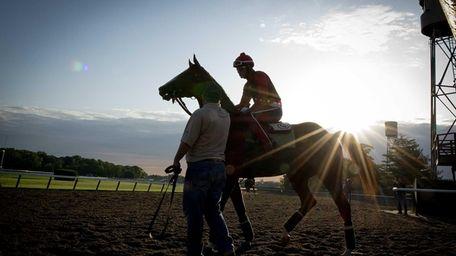 Exercise rider Willie Delgado taking California Chrome for