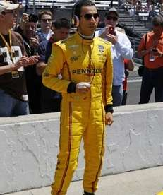 Helio Castroneves, of Brazil, listens to music as