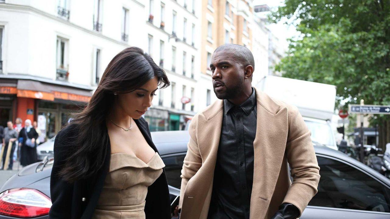 Kanye West and Kim Kardashian walk through rue