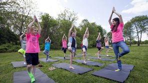 Kids practice yoga with camp counselor Amanda Mattera