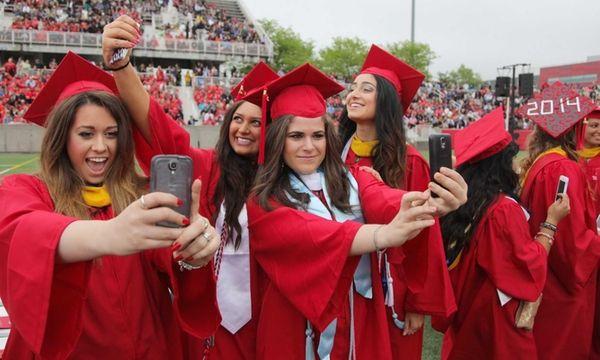 Graduates take selfies during the Stony Brook University
