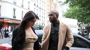 Kanye West and Kim Kardashian walk through rue