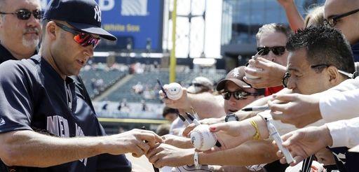 Yankees' Derek Jeter, left, signs autographs for fans