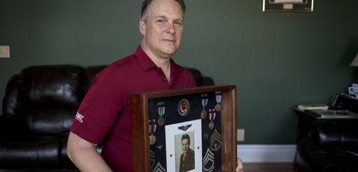 Wayne Howard, of Amityville, holds a memorabilia box