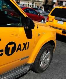 Two gas-electric hybrid taxi cabs drive on a