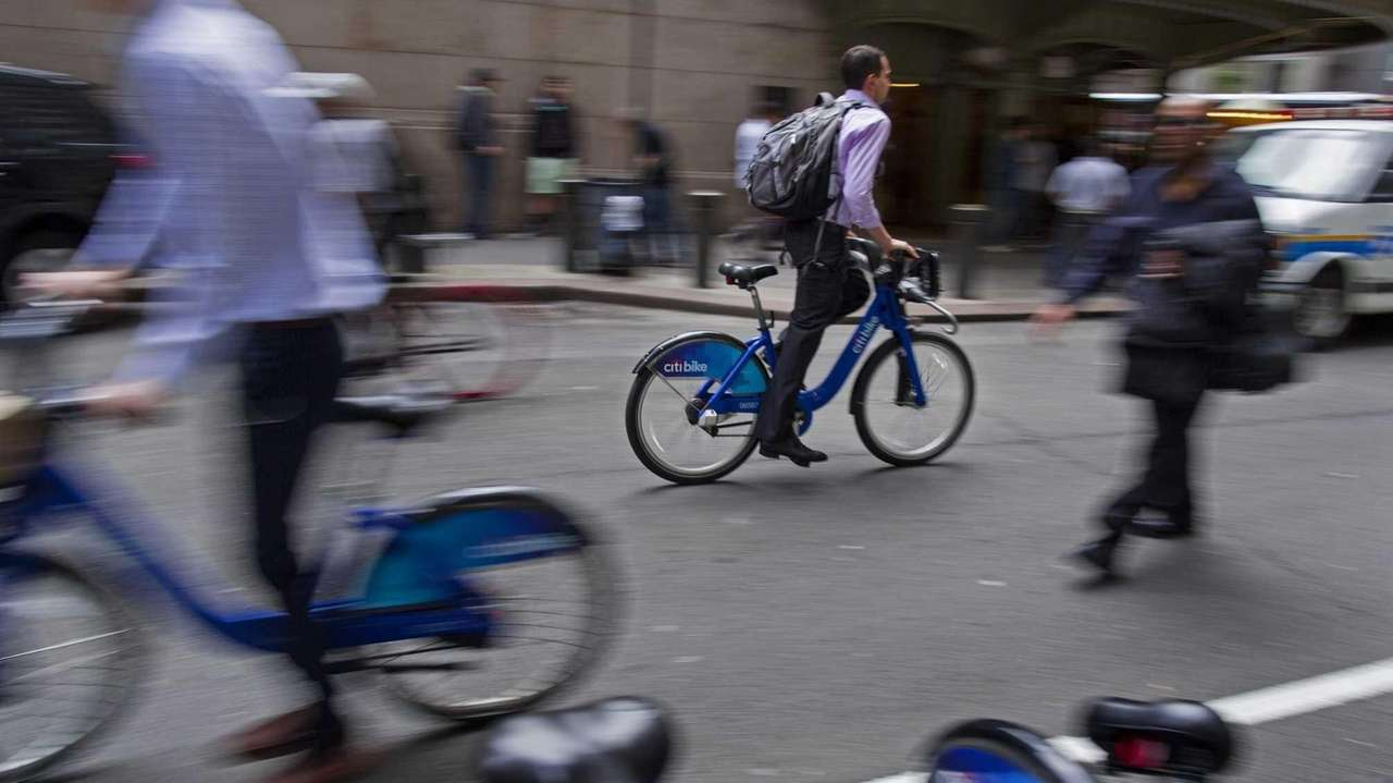 Citi Bikes riders pass by a Citi Bike