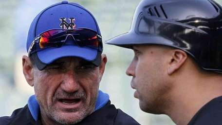 Mets batting coach Dave Hudgens, left, talks with