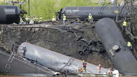 Survey crews in boats look over tanker cars
