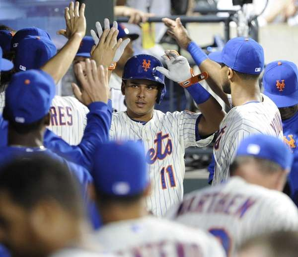 Mets' Ruben Tejada is congratulated in the dugout