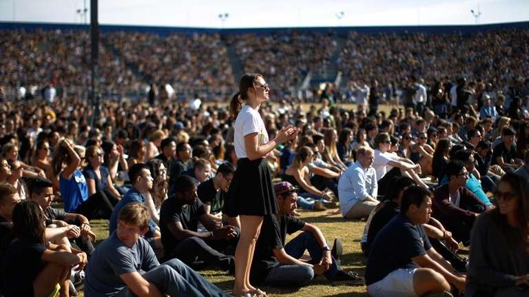 Students mourn at a public memorial service on