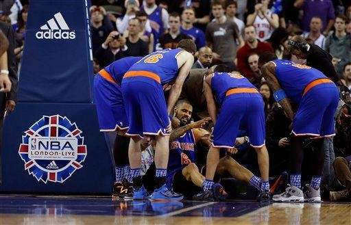 Knicks center Tyson Chandler, bottom, is helped back