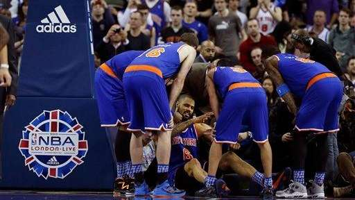 Knicks center Tyson Chandler, bottom, is helped back