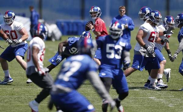 Giants quarterback Eli Manning, center, looks to pass