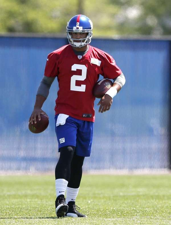 Giants quarterback Josh Freeman holds footballs during an