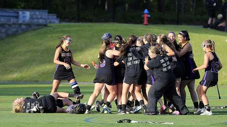 Sayville girls lacrosse players storm the field after