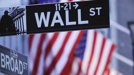 American flags hang behind a Wall Street sign
