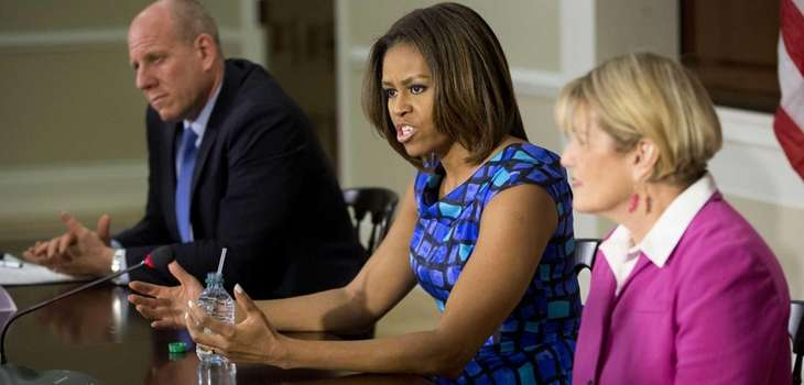 First lady Michelle Obama, seated with Eric Goldstein,