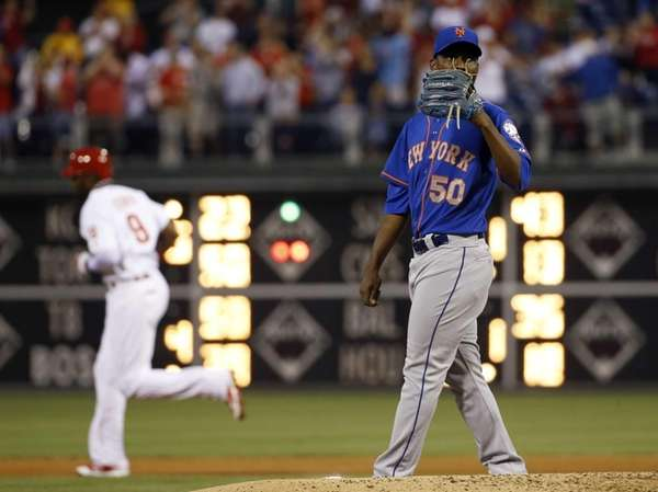 Mets starting pitcher Rafael Montero, right, wipes his