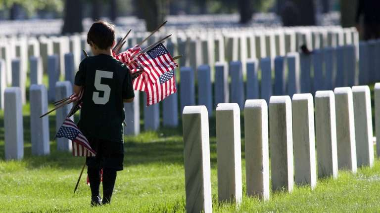 Patrick Cottone, 5, from Farmingdale, picks up flags