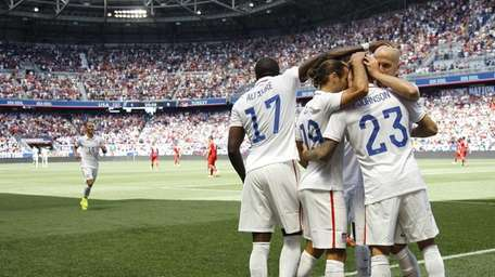 The United States' Fabian Johnson (23) is congratulated
