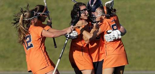 Manhasset players surround their goalie Erin Coleman (42)