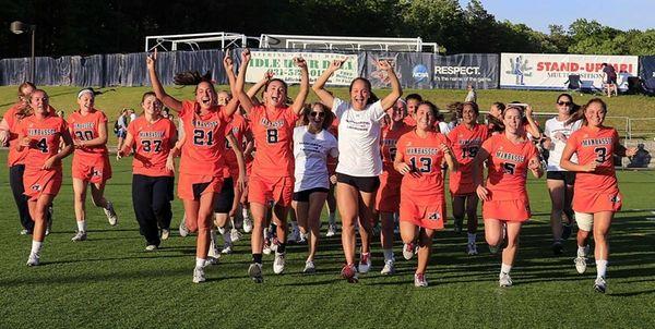 The Manhasset girls lacrosse team runs across the