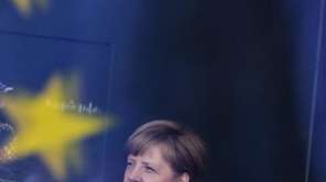 German Chancellor Angela Merkel stands behind a window