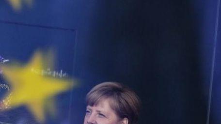 German Chancellor Angela Merkel stands behind a window