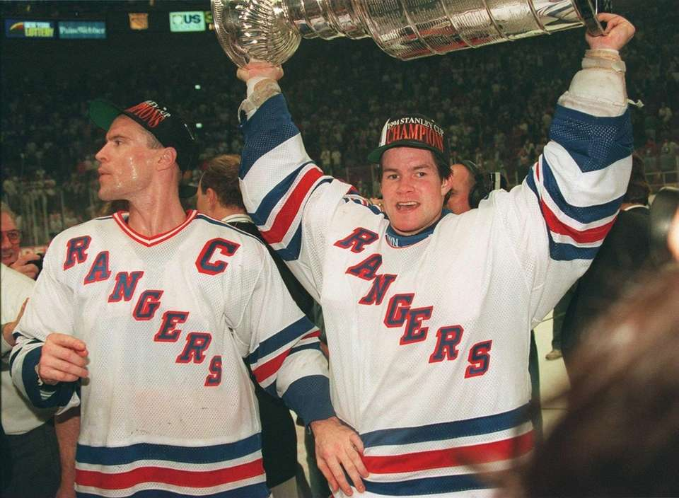 Rangers goalie Mike Richter, right, raises the Stanley