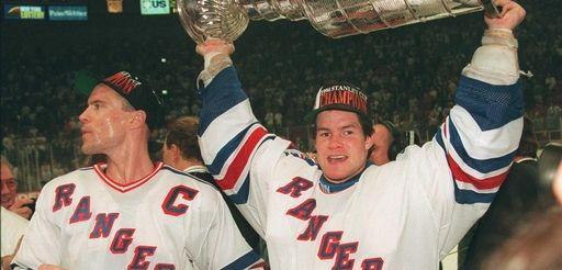 Rangers goalie Mike Richter, right, raises the Stanley