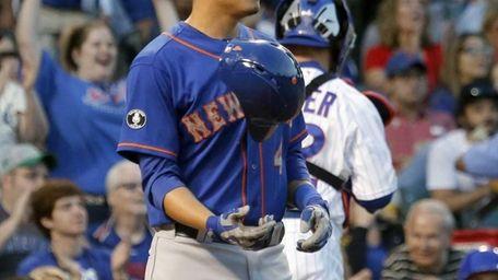 The Mets' Wilmer Flores flips his helmet after