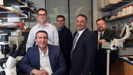 Mark Lesko, of Accelerate Long Island, seated, with,