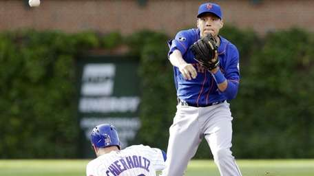 Mets second baseman Wilmer Flores throws to first