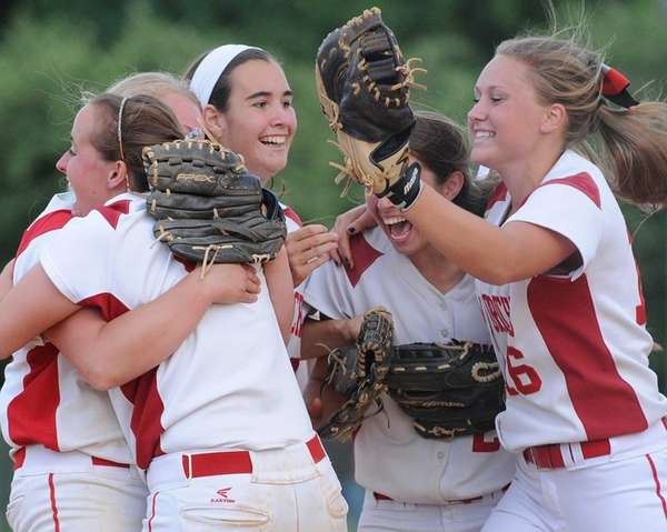 Center Moriches 3B Erin Copozzi, facing, and teammates