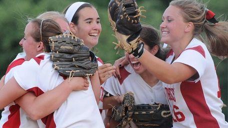 Center Moriches 3B Erin Copozzi, facing, and teammates