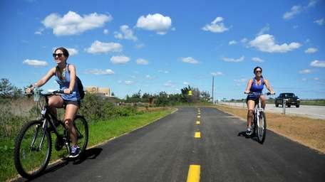 Bikers ride along a newly opened section of