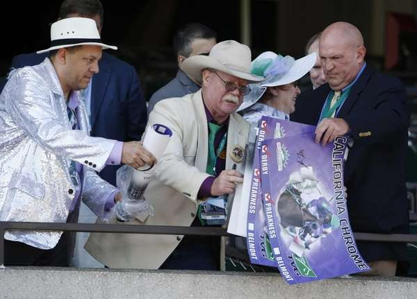 California Chrome co-owner Steve Coburn, center, reaches for